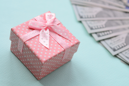 Pink dotted gift box lies near hundred dollar bills on a light blue background.