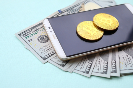 Bitcoins lies on a smartphone and hundred dollar bills on a light blue background. Stock Photo