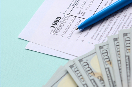 1065 tax form lies near hundred dollar bills and blue pen on a light blue background. US Return for parentship income.