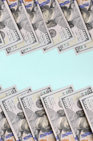 Row of a US dollar bills of a new design lies on a light blue background.