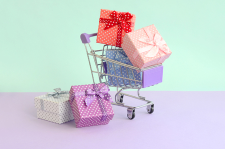 Small gift boxes of different colors with ribbons lies in shopping cart on a violet and blue pastel background. Stock Photo