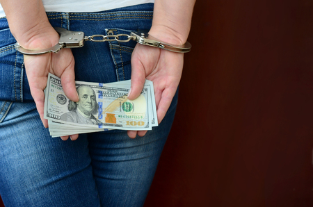 An arrested girl with handcuffed hands with a huge amount of dollar bills. Back view.