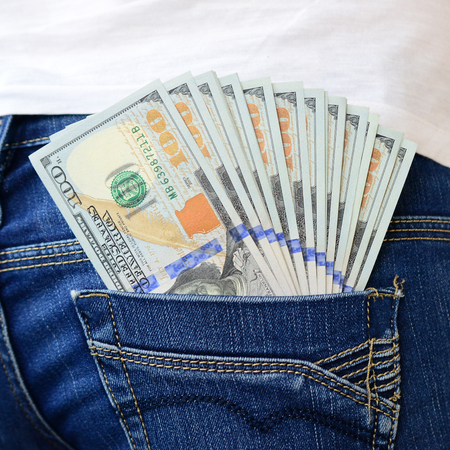A large number of dollar bills lies in the back pocket of the girls jeans.