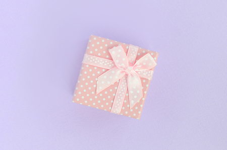 Small pink gift box with ribbon lies on a violet background. Minimalism flat lay top view.