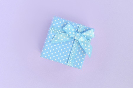Small blue gift box with ribbon lies on a violet background. Minimalism flat lay top view.