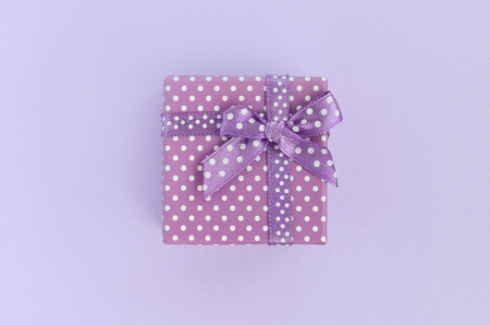 Small purple gift box with ribbon lies on a violet background. Minimalism flat lay top view.