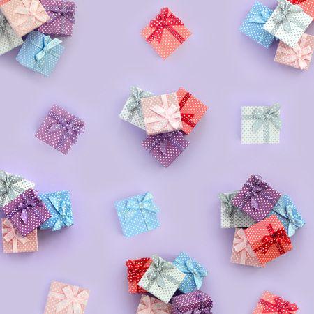 Piles of a small colored gift boxes with ribbons lies on a violet background. Minimalism flat lay top view pattern. Stock Photo