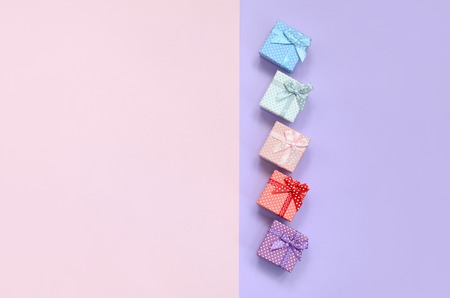 Small gift boxes of different colors with ribbons lies on a violet and pink color background. Stock Photo