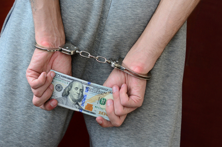 An arrested guy in gray pants with handcuffed hands holds a huge amount of dollar bills. Back view.