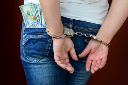 An arrested girl with handcuffed hands with a huge amount of dollar bills. Back view. Stock fotó