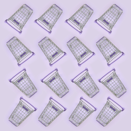 Pattern of many small shopping carts on a violet background. Minimalism flat lay top view.