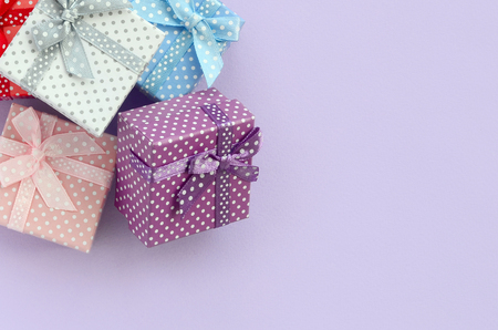 Pile of a small colored gift boxes with ribbons lies on a violet background. Minimalism flat lay top view.