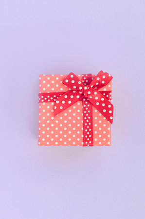 Small red gift box with ribbon lies on a violet background. Minimalism flat lay top view. Stock Photo