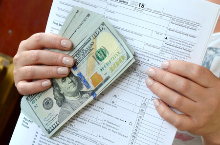 The girl holds in her hands the tax form and a large number of dollar bills.