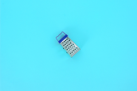 Stainless steel grater lies on a pastel colored paper. Kitchen accessories. Tools for cooking. Flat lay top view. Stock Photo
