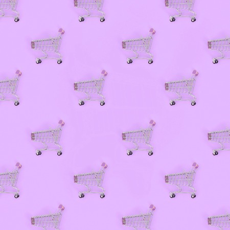Shopping addiction, shopping lover or shopaholic concept. Many small empty shopping carts perform a pattern on a pastel colored paper background. Flat lay composition, top view.