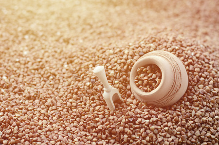 Background image of a large pile of buckwheat, in the middle of which lies a small jug and a wooden spatula for cereals Stock Photo