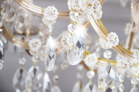 Close-up photo of the scenery on the old chandelier. Glass figures shine and reflect light with their faces Stock fotó