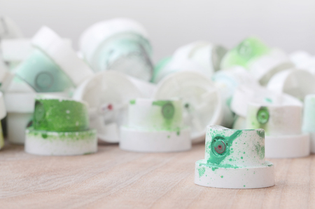 Several plastic nozzles from a paint sprayer that lie on a wooden surface against a gray wall background. The caps are smeared in green paint. The concept of street art and graffiti Stock fotó