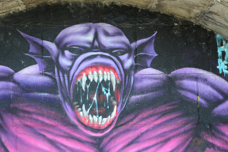 Fragment of graffiti drawings. The old wall decorated with paint stains in the style of street art culture. Purple scary monster. Stock Photo