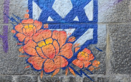 Fragment of graffiti drawings. The old wall decorated with paint stains in the style of street art culture. Orange flower.