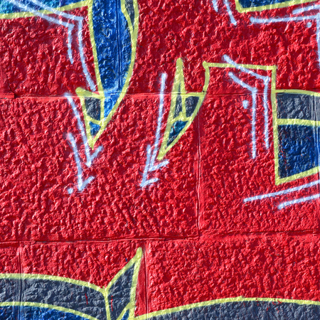 Fragment of graffiti drawings. The old wall decorated with paint stains in the style of street art culture. Colored background texture in warm tones.