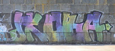 Fragment of graffiti drawings. The old wall decorated with paint stains in the style of street art culture. Multicolored background texture.
