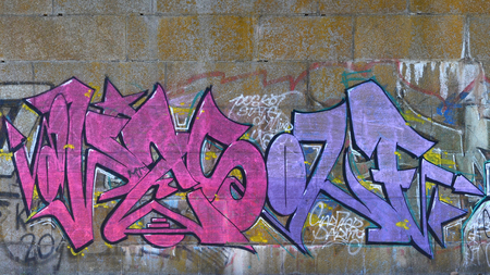 Fragment of graffiti drawings. The old wall decorated with paint stains in the style of street art culture. Colored background texture in purple tones. Stock Photo