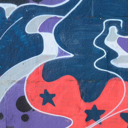 Fragment of graffiti drawings. The old wall decorated with paint stains in the style of street art culture. Colored background texture in cold tones.