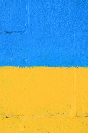 Fragment of graffiti drawings. The old wall decorated with paint stains in the style of street art culture. Ukrainian flag. Stock Photo