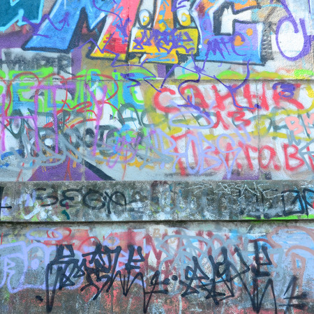 Fragment of graffiti tags. The old wall is spoiled with paint stains in the style of street art culture. Stock Photo