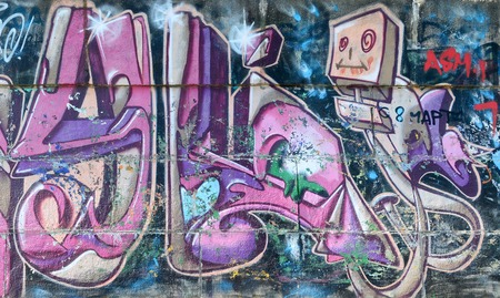 Fragment of graffiti drawings. The old wall decorated with paint stains in the style of street art culture. Colored background texture in purple tones. Reklamní fotografie