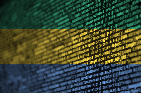 Gabon flag  is depicted on the screen with the program code. The concept of modern technology and site development.