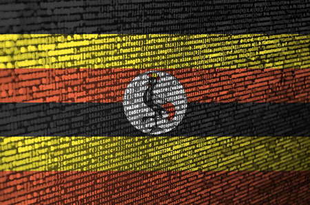 Uganda flag  is depicted on the screen with the program code. The concept of modern technology and site development. Stock Photo
