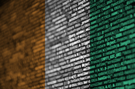 Ivory Coast flag  is depicted on the screen with the program code. The concept of modern technology and site development.