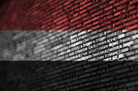 Yemen flag  is depicted on the screen with the program code. The concept of modern technology and site development.