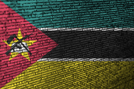 Mozambique flag  is depicted on the screen with the program code. The concept of modern technology and site development. Stok Fotoğraf