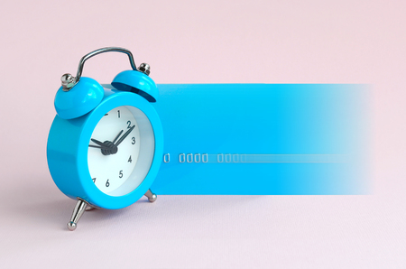 Small blue alarm clock is next to blue credit card in motion. The concept of modern fast online banking and instant financial operations 스톡 콘텐츠