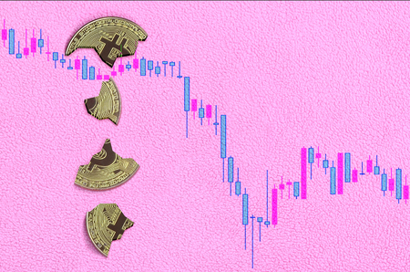 Broken bitcoin lies in the background of the falling chart of the cryptocurrency rate. Pastel pink background. Flat lay top view. The fall and collapse of the course of crypto currency