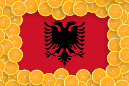 Albania flag  in frame of orange citrus fruit slices. Concept of growing as well as import and export of citrus fruits