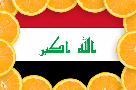 Iraq flag  in frame of orange citrus fruit slices. Concept of growing as well as import and export of citrus fruits