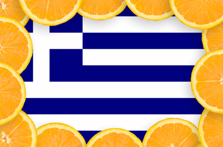 Greece flag  in frame of orange citrus fruit slices. Concept of growing as well as import and export of citrus fruits Banco de Imagens