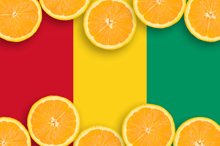 Guinea flag  in horizontal frame of orange citrus fruit slices. Concept of growing as well as import and export of citrus fruits