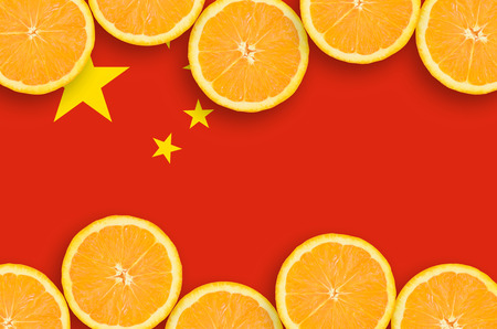 China flag  in horizontal frame of orange citrus fruit slices. Concept of growing as well as import and export of citrus fruits