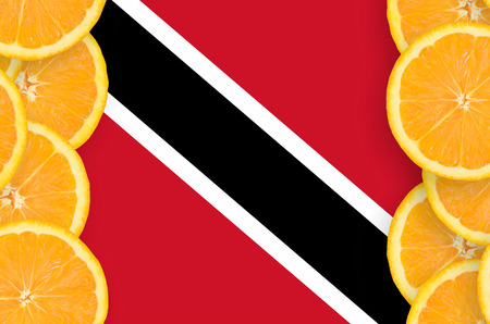 Trinidad and Tobago flag  in vertical frame of orange citrus fruit slices. Concept of growing as well as import and export of citrus fruits Stock Photo