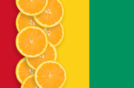Guinea flag and vertical row of orange citrus fruit slices. Concept of growing as well as import and export of citrus fruits Stock fotó