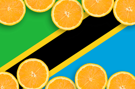 Tanzania flag in horizontal frame of orange citrus fruit slices. Concept of growing as well as import and export of citrus fruits