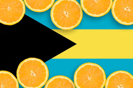 Bahamas flag  in horizontal frame of orange citrus fruit slices. Concept of growing as well as import and export of citrus fruits
