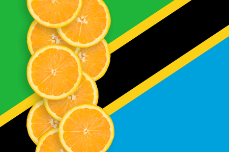 Tanzania flag and vertical row of orange citrus fruit slices. Concept of growing as well as import and export of citrus fruits Foto de archivo - 114930121