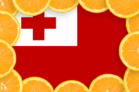 Tonga flag  in frame of orange citrus fruit slices. Concept of growing as well as import and export of citrus fruits 스톡 콘텐츠